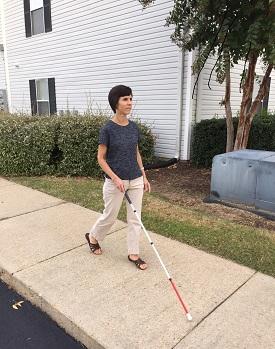 Kendra using white cane on sidewalk