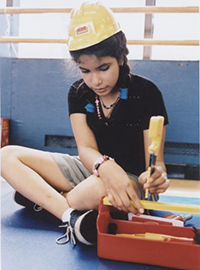 girl playing with plastic tools, wearing construction hat
