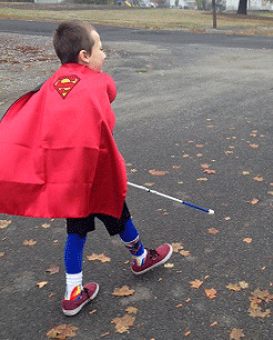Eddie dressed as Superman, walking with his white cane