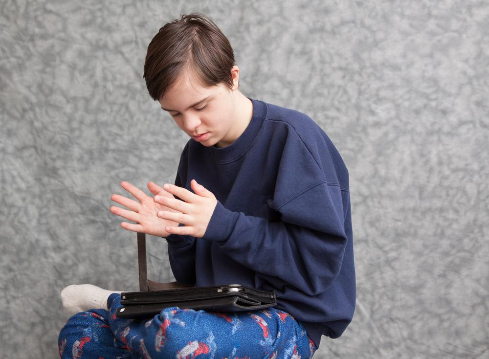 Image of a boy sitting with legs crossed, an iPad on his lap. His hands are clapping in the air.