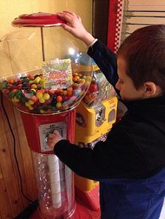 Eddie putting money in a giant gumball machine