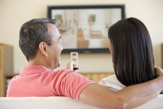 Asian couple smiling while watching TV