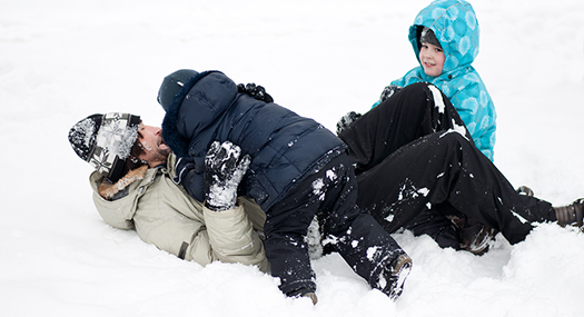 parent and two children playing in the snow