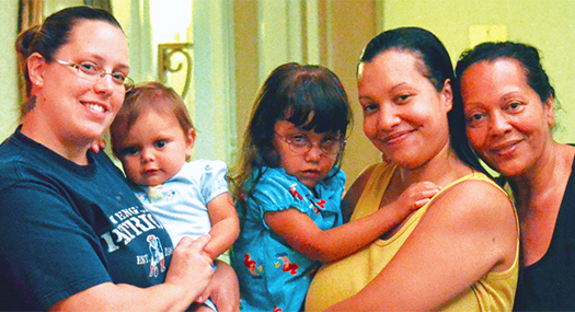 three women, two of whom are holding young children