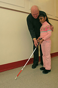 An orientation and mobility instructor working with a school-aged girl