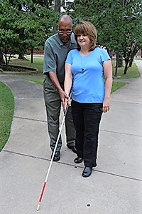 male orientation and mobility instructor shows a woman how to use her white cane