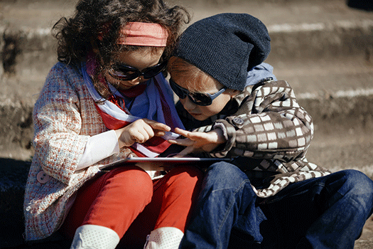 little girl and boy, both wearing sunglasses, playing with an iPad outside