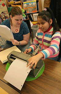 girl using braillewriter in the classroom, with her teacher looking on