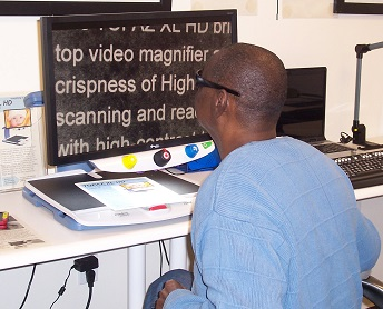 man reading with video magnifier