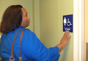 empish reading braille sign on bathroom