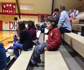 Eddie Sitting in Bleachers at Basketball Game