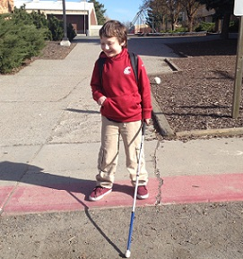 Eddie with white cane standing outside his school