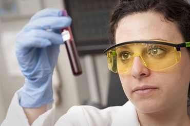 lab tech examines vial of blood image credit to National Eye Institute