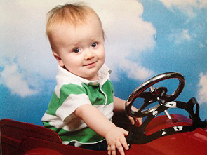 Eddie as baby sitting up in toy car