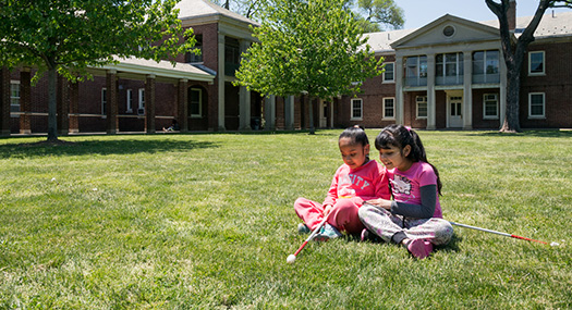 two young girls sit on the grass, enjoying the sunshine, their white canes in their lap