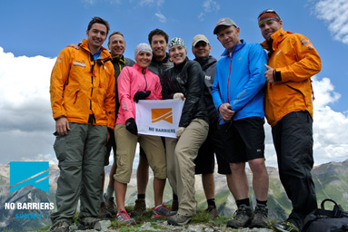 Group of men and women posing on a mountain summit with the No Barrier sign