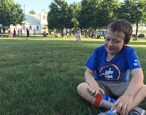 Eddie sitting on grass at park in front of softball game
