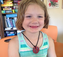 Child wearing a home-made necklace