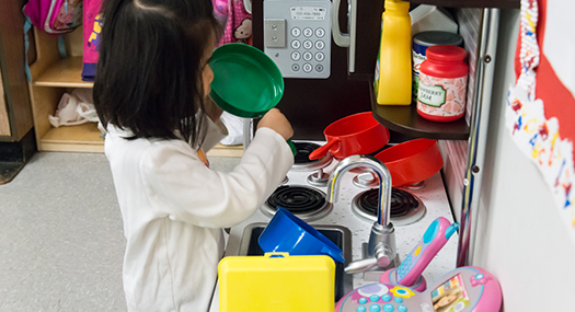 Girl playing in a pretend kitchen
