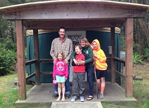 Family standing in front of a yurt (round dwelling)