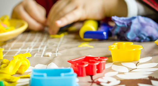 closeup of child's hands playing with colorful dough and plastic molds