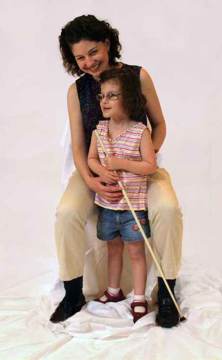 Mother with young daughter, who is wearing glasses and holding a white cane