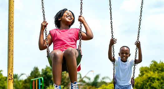 A girl and boy swinging, big smiles on their faces