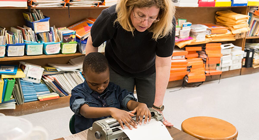 A teacher leans over her student to check his work on the braille printer