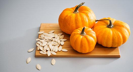 three mini pumpkins and seeds on a cutting board