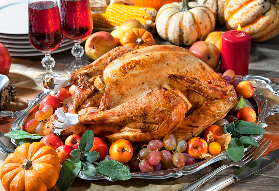 Thanksgiving dinner. Roasted turkey on holiday table with pumpkins, candles, and fruit