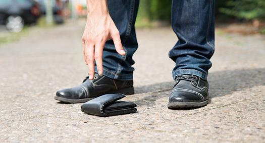 man reaching for fallen wallet on the sidewalk