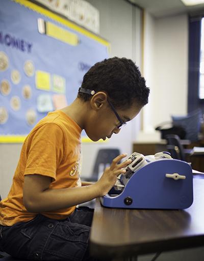 child at braillewriter