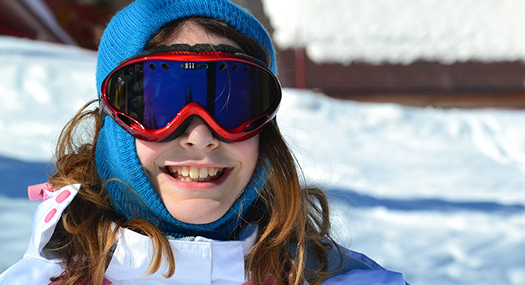 Young girl smiling, wearing protective snow goggles on a ski slope