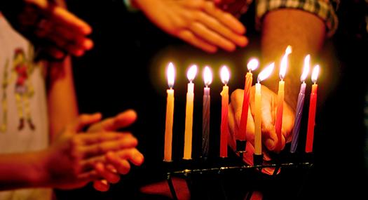 hands of family members around a lit Menorah