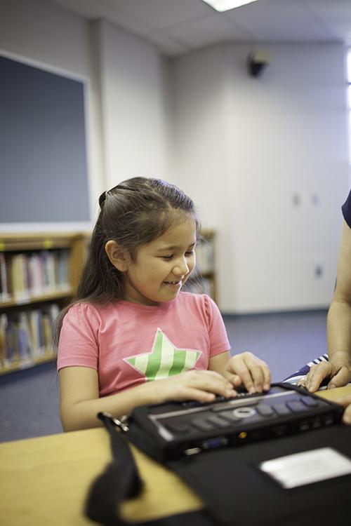 girl using braille notetaker
