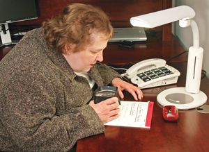 Woman sitting at   desk using a magnifier to read a notepad. A bright table lamp lights the   entire desktop.