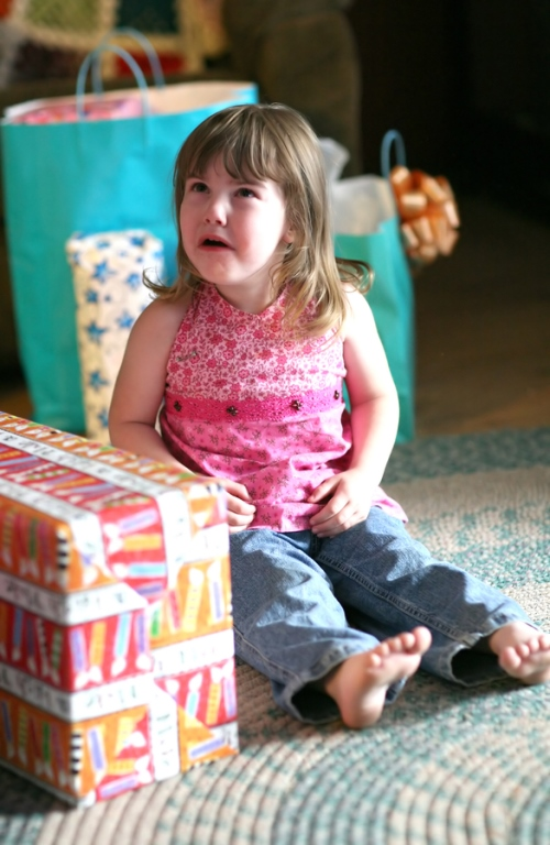 A young girl sits surrounded by gifts. She is crying.