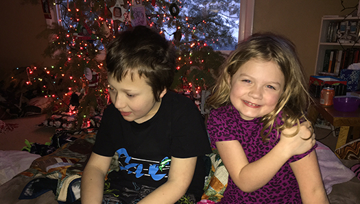 Eddie and his sister CC sitting in front of a decorated Christmas tree