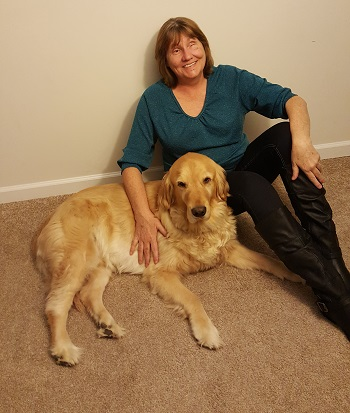 woman seated on floor with arm around dog guide