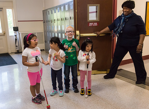 four children, two with canes, two without, smiling as their orientation and mobility instructor holds the door open for them
