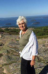 Judith Millman, smiling in a beautiful coastal setting