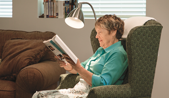 Woman sitting   in chair reading magazine. A bright floor lamp over the magazine and full   light enters from the window behind her.