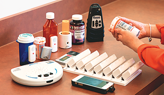 A woman holding a pill bottle in her hand. A variety of medications   are on a table in front of her.