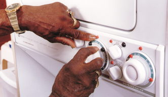 A person using raised bumps on washer to adjust the   settings.