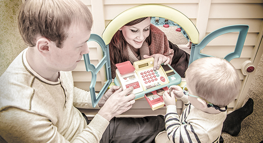 Parents play with their child and a pretend cash register