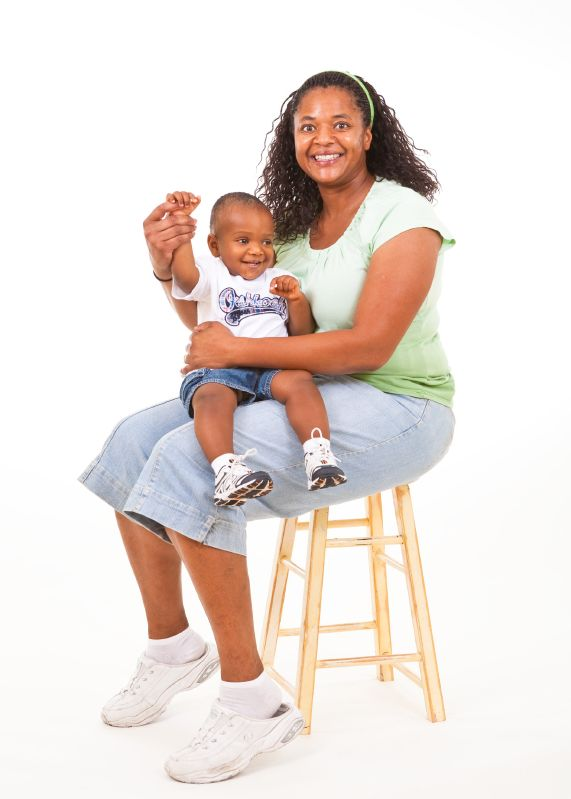 mom with son on her lap - both are smiling widely, and the mom is holding her child's hand up high