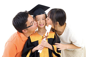 Kindergarten child in graduation gown and mortarboard kissed by her parents during graduation