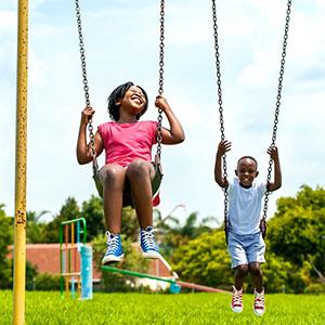 Kids having fun swinging in park