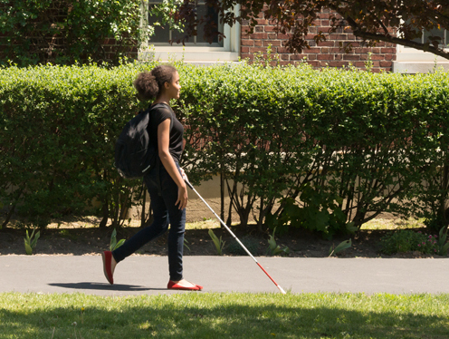 Teenage girl wearing a backpack and walking with white cane on sunny day