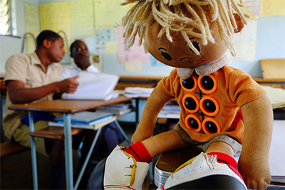 Image of a Braille Learning Doll with six buttons on the doll's stomach